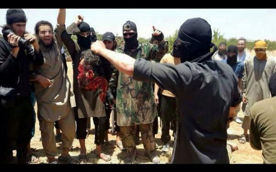 A Jabhat al-Nusra fighter holding the severed head of a Hezbollah fighter in Qalamoun.